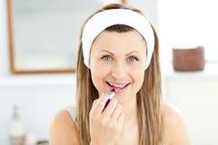 使用妇女年轻人的高兴唇膏红色 免版税库存图片