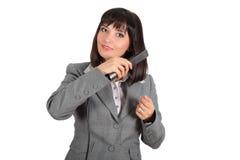 使用妇女年轻人的头发直挺器 免版税库存图片