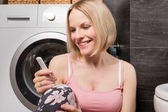 使用妊娠试验的愉快的少妇在卫生间 免版税图库摄影