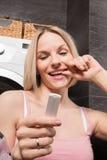 使用妊娠试验的愉快的少妇在卫生间 图库摄影