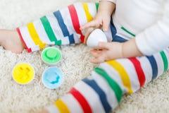 使用婴孩的特写镜头使用与教育五颜六色的形状整理者玩具 库存图片