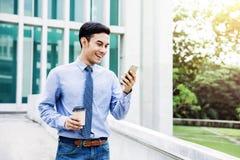使用室外一个巧妙的电话的愉快的年轻商人,沟通 免版税库存照片