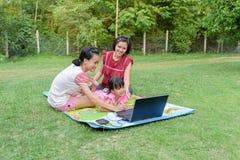 使用室外的膝上型计算机的微笑的家庭 免版税库存图片