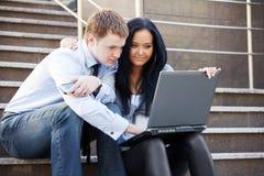 使用室外的膝上型计算机的年轻企业夫妇 免版税图库摄影