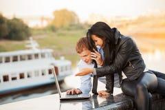 使用室外的膝上型计算机的年轻企业夫妇 图库摄影