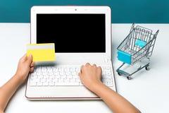 使用对网上购物和薪水的膝上型计算机由信用卡 葡萄酒口气,减速火箭的过滤器作用 免版税库存照片
