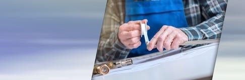 使用封印磁带的水管工的手,光线影响 全景banne 库存照片