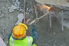 使用小型发焰装置的工作者对切开金属在建造场所 免版税库存图片