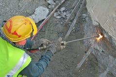 使用小型发焰装置的工作者对切开金属在建造场所 库存照片