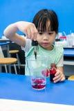 使用小滴的幼儿园女孩增加红颜色入在b的一个杯子 免版税库存照片