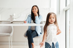 使用小逗人喜爱的亚裔的女孩,当她的母亲工作时 免版税图库摄影