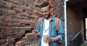 使用小配件智能手机的阿拉伯人的慢动作拿着咖啡户外 影视素材