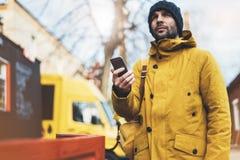 使用小配件机动性,有黄色背包的,夹克,盖帽,举行在手智能手机的热杯子咖啡行家,做自由职业者 免版税库存照片