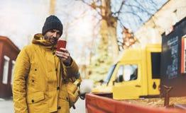 使用小配件机动性,有黄色背包的,夹克,盖帽,举行在手智能手机的热杯子咖啡行家,做自由职业者 免版税库存图片
