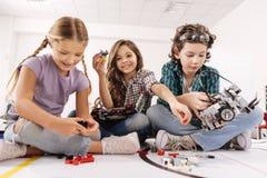 使用小配件和设备的聪明的孩子在演播室 库存照片