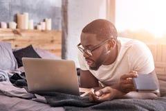 使用小配件的创造性的年轻非裔美国人在家 免版税库存图片