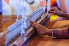 使用小织布机或织机的织布工为机织织物 W 免版税库存照片