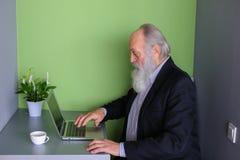 使用尖头棒,退休的老练的商人通过skype沟通 库存照片