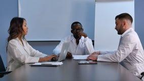 使用工作的膝上型计算机的微笑的医疗队,谈论新的医学 库存照片