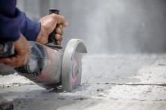 使用工具的工作者切开与空白的水泥地板在右边 库存图片