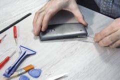 使用工具,人的手去除手机的盖子 免版税图库摄影