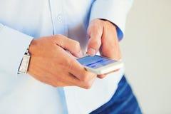 使用巧妙的手机的年轻英俊的人, 免版税库存照片