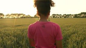 使用巧妙的手表和赛跑在道路的混合的族种非裔美国人的女孩少年母少妇赛跑者通过大麦的领域 影视素材