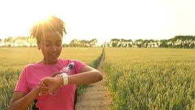 使用巧妙的手表和赛跑在道路的混合的族种非裔美国人的女孩少年母少妇赛跑者通过领域在日落 股票视频
