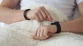 使用巧妙的手表的人,当在家时说谎在床 股票视频