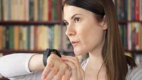 使用巧妙的手表的女性大学生在图书馆,口授音频消息对朋友通过信使 影视素材
