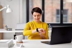 使用巧妙的手表的愉快的女实业家在办公室 免版税库存图片