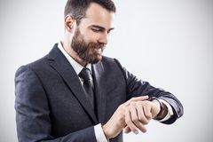 使用巧妙的手表的英俊的年轻商人 图库摄影