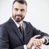 使用巧妙的手表的英俊的年轻商人 免版税库存照片