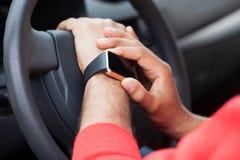 使用巧妙的手表的非洲人的手坐在汽车 库存照片