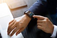 使用巧妙的手表app的商人手在膝上型计算机和智能手机在运作的书桌、技术和通信概念 所有在s 库存图片