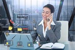 使用巧妙的电话和膝上型计算机有象的愉快的女实业家的数字式综合图象在前景 免版税库存图片