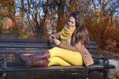 使用巧妙的电话在公园 免版税库存图片