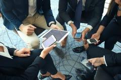使用巧妙的电话坐在会议上,关闭的人在手上 免版税库存图片