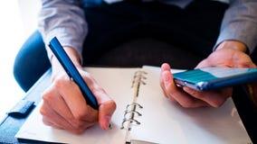 使用巧妙的电话并且做在笔记本的笔记 免版税库存照片