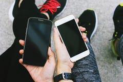 使用巧妙的电话的两个女孩在户外 免版税库存照片