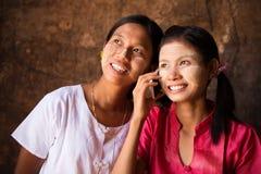 使用巧妙的电话的两个缅甸女孩。 免版税库存图片