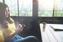使用巧妙的电话的亚裔妇女在咖啡店 免版税图库摄影