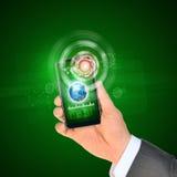 使用巧妙的电话的人手 在电话屏幕上的地球 库存图片