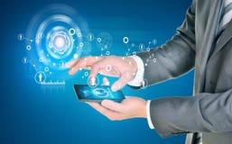 使用巧妙的电话的人手 在电话屏幕上的地球 免版税库存图片