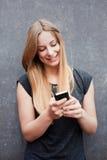 使用巧妙的电话的十几岁的女孩 库存图片