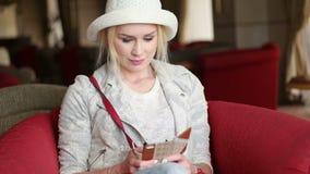 使用巧妙的电话的可爱的白肤金发的女商人 影视素材