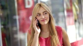 使用巧妙的电话的可爱的年轻白肤金发的夫人在城市购物中心 股票视频