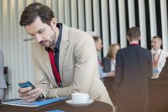 使用巧妙的电话的商人,当咖啡休息在会议中心时 免版税库存照片