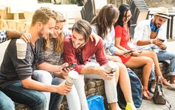 使用巧妙的电话的多种族millennials小组在城市学院 免版税库存照片