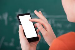 使用巧妙的电话的大学生在教室 免版税库存图片